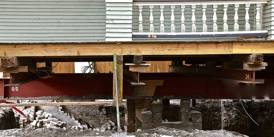 an old house rests on steel girders as a new concrete basement and foundation is being created