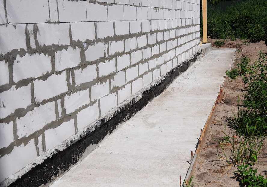 waterproofing and insulation unfinished house foundation wall.